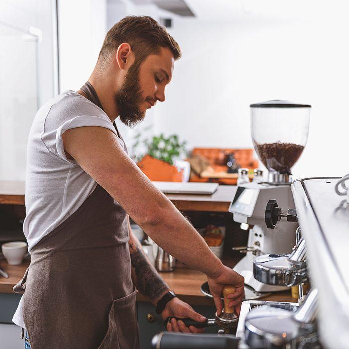 bearded barista tamping ground coffee; Shutterstock ID 520565953; Job (TFH, TOH, RD, BNB, CWM, CM): TOH